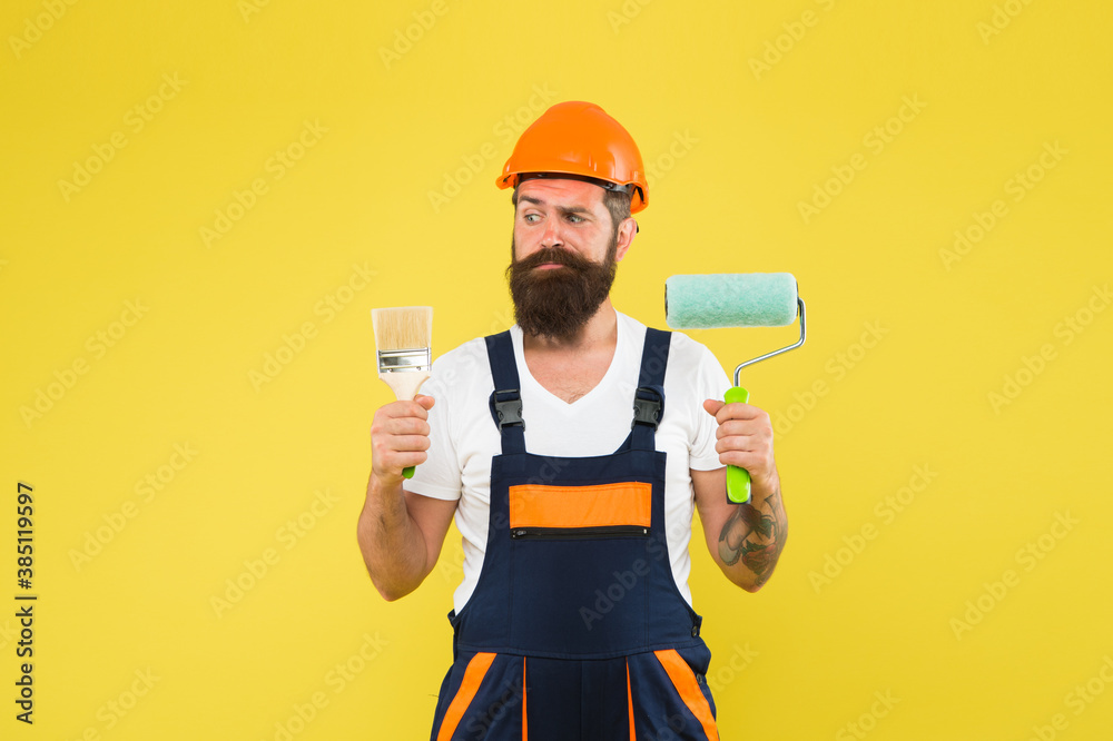 Fototapeta Skilled painter with serious look in working overalls hold paint brush and roller for painting work under construction, professional