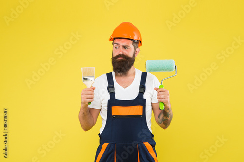 Obraz Skilled painter with serious look in working overalls hold paint brush and roller for painting work under construction, professional - fototapety do salonu