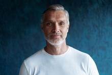 Casual Grey-haired Mature Handsome Man Portrait Over Dark Blue Wall Background