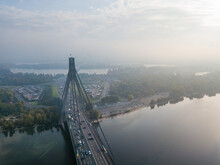 Aerial Drone View. North Bridge In Kiev In The Rays Of A Sunny Morning. Autumn Haze In The Air, Cars Are Driving Across The Bridge.
