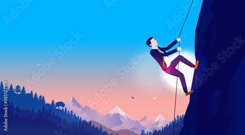 Fototapeta Climb to success - Determined businessman climbing rope up dangerous mountain