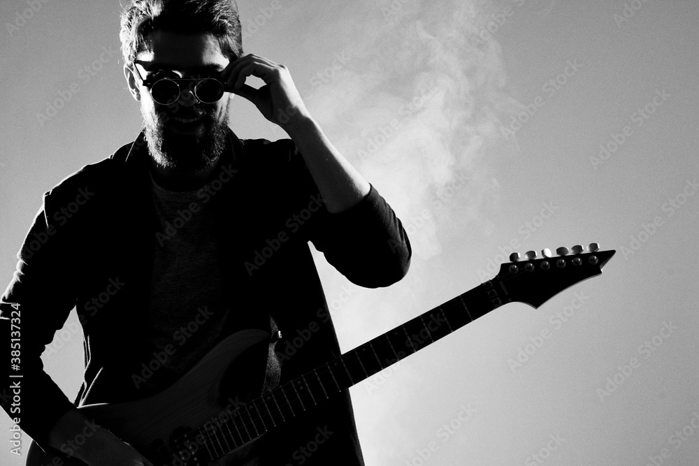 Fototapeta Male musician with guitar music rock star light background