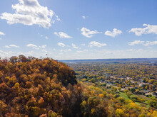 Autumn Landscape Of The Bluffs In Lacrosse, Wisconsin With Trees And Clouds Over Granddads Bluff With A Flag Flying High