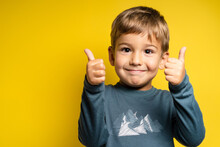 Portrait Of Happy Small Caucasian Boy In Front Of Yellow Background Thumbs Up - Childhood Growing Up And Achievement Concept - Front View Waist Up Copy Space