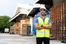 Portrait Of Young Indian Worker With Arm Folded Working In Logistic Industry Outdoor In Front Of Factory Warehouse. Smiling Happy Man In Hard Hat Looking At Camera Arms Crossed At Depot