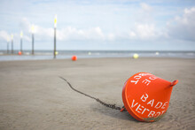 Red Buoy Lying On Beach Sand