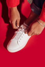 Woman Tying Shoe Lace On Red B...