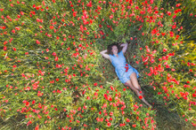Young Woman With Hands Behind Head Lying On Poppy Field