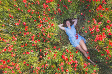 Smiling Woman Lying With Hands Behind Head On Poppy Field