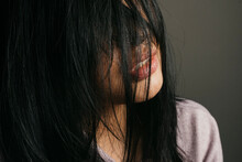 Close-up Of Woman With Messy Black Hair Against Wall