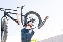Male Amputee Cyclist With Arms Raised Carrying Bicycle While Standing Against Clear Sky