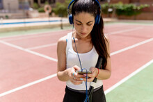 Female Tennis Player Using Smart Phone While Listening Music In Court On Sunny Day
