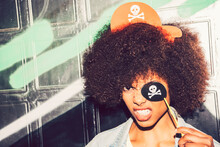 Close-up Of Woman Clenching Teeth While Holding Fake Pirate Eye Patch Against Wall