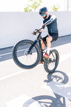 Male Amputee Athlete Performing Stunt With Bicycle On Road During Sunny Day