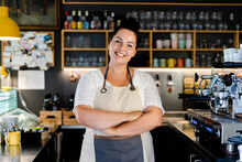 Smiling Female Barista With Ar...