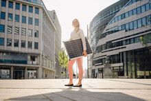 Smiling Beautiful Female Entrepreneur Holding Solar Panel While Standing On Footpath In Financial District