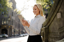 Smiling Blond Female Professional Using Digital Tablet While Leaning On Surrounding Wall In City