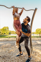 Man Supporting Woman Lifting Herself Up On A Fitness Trail