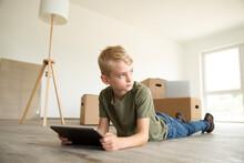 Boy Using Digital Tablet Looki...