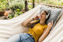 Woman With Eyes Closed Listening Music Through Headphones While Relaxing On Hammock In Yard