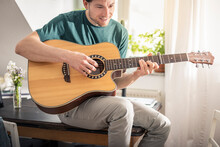Smiling Man Playing Guitar Whi...