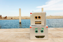 Robot Masks Made Of Boxes On Footpath Against Water