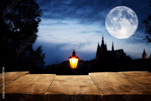 Obraz Halloween Holiday concept. Empty rustic table in front of scary night sky, forest and full moon background. Ready for product display montage - fototapety do salonu
