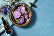 Aromatherapy Concept. Essential Oil Bottle, Incense Cone, Scented Candle With Verbena And Lavender, Overhead Shot With Copy Space On A Blue Background