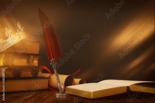 low key image of beautiful queen/king crown over old book and feather quill ink pen over wooden table Fototapet