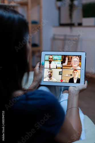 Foto Having online meeting using tablet laying on comfortable sofa at home