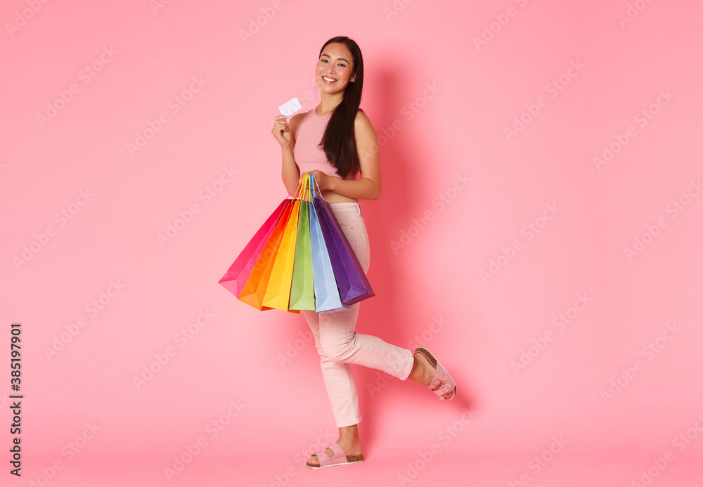 Fototapeta Full length portrait of upbeat and excited, smiling trendy asian girl showing her credit card and looking pleased, carry shopping bags, bought new clothes for vacation, pink background