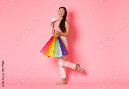 Fototapeta Full length portrait of upbeat and excited, smiling trendy asian girl showing her credit card and looking pleased, carry shopping bags, bought new clothes for vacation, pink background obraz