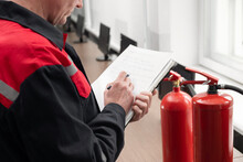 Engineer Professional Are Checking A Fire Extinguisher And Writes Data To The Check Log. Fire Alarm Controller.System Ready In The Event Of A Fire.