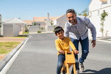 Indian Father Helping Son Riding Bike Outdoor