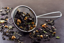 Metal, Aluminum Infusion Filter Filled With Dry Tea Made From Fruits And Herbs And Flowers, Black Background. Healthy And Tasty Tea.