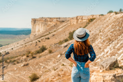 Rear view of a young woman in a plaid shirt and hat standing on a mountain and a Wallpaper Mural