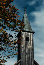 Black Church Bell Tower, Ominous In The Background, Autumn Tree Branch In Front Of It