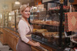 Beautiful female baker welcoming you at her bakery store, copy space
