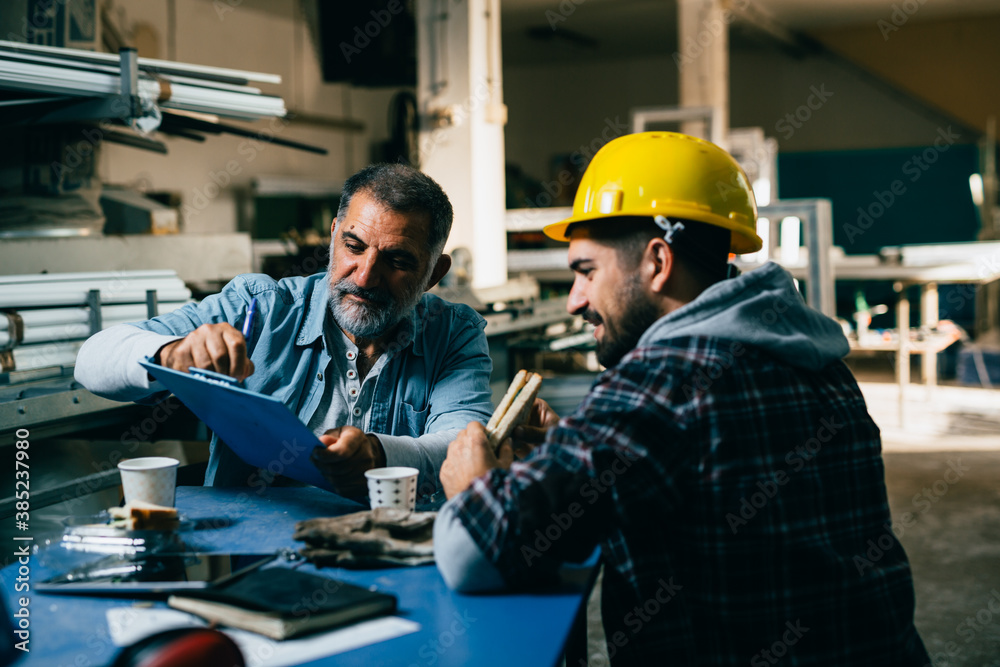 Fototapeta industrial workers on lunch break at the warehouse