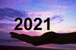 Hand offering 2021 numbers, beach sunset background, new year and holidays greeting card