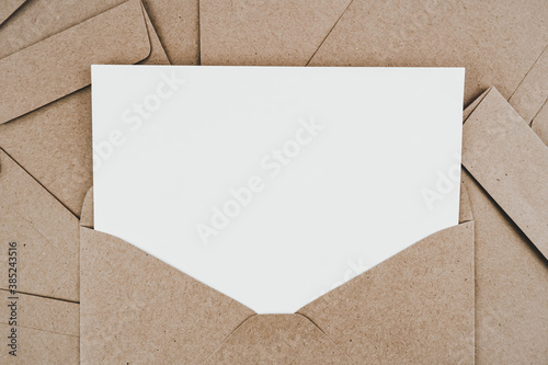 Obraz Blank white paper is placed on the open brown paper envelope. Mock-up of horizontal blank greeting card. Top view of Craft paper envelope on white background. Flat lay of stationery. Minimalism style. - fototapety do salonu