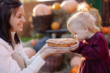 Small Happy Family Celebrating Thanksgiving. Mom Feeds Her Daughter Sweet Pie. Funny Toddler Eating With A Good Appetite. Fun Photo Curiosity. Harvesting Eco Nature Gifts Autumn. Countryside Lifestyle