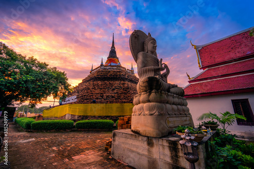 PHITSANULOK, THAILAND - October 10,2020:Buddha statue and Phra Chedi Luang in Temple (Thai language:Wat Ratchaburana) is a Buddhist temple It is a major tourist attraction in Phitsanulok, Thailand Wallpaper Mural