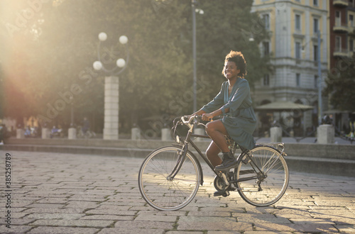 young woman cycling in the city Canvas