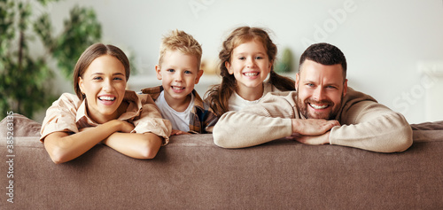 happy family mother father and children at home on couch . - 385263135