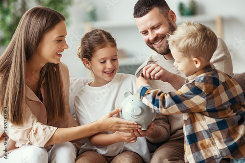 Photo financial planning   family mother father and children with piggy Bank at home
