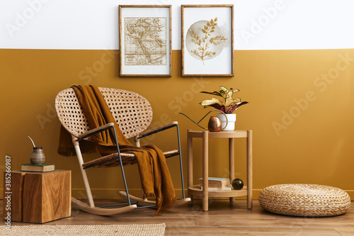 Obraz Stylish composition of living room interior with design rattan armchair, two mock up poster frames, plants, cube, palid and personal accessories in honey yellow home decor. Template. - fototapety do salonu