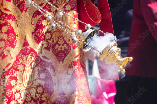 A smoking censer in the hand of an Orthodox Christian priest in an embroidered church cassock Wallpaper Mural