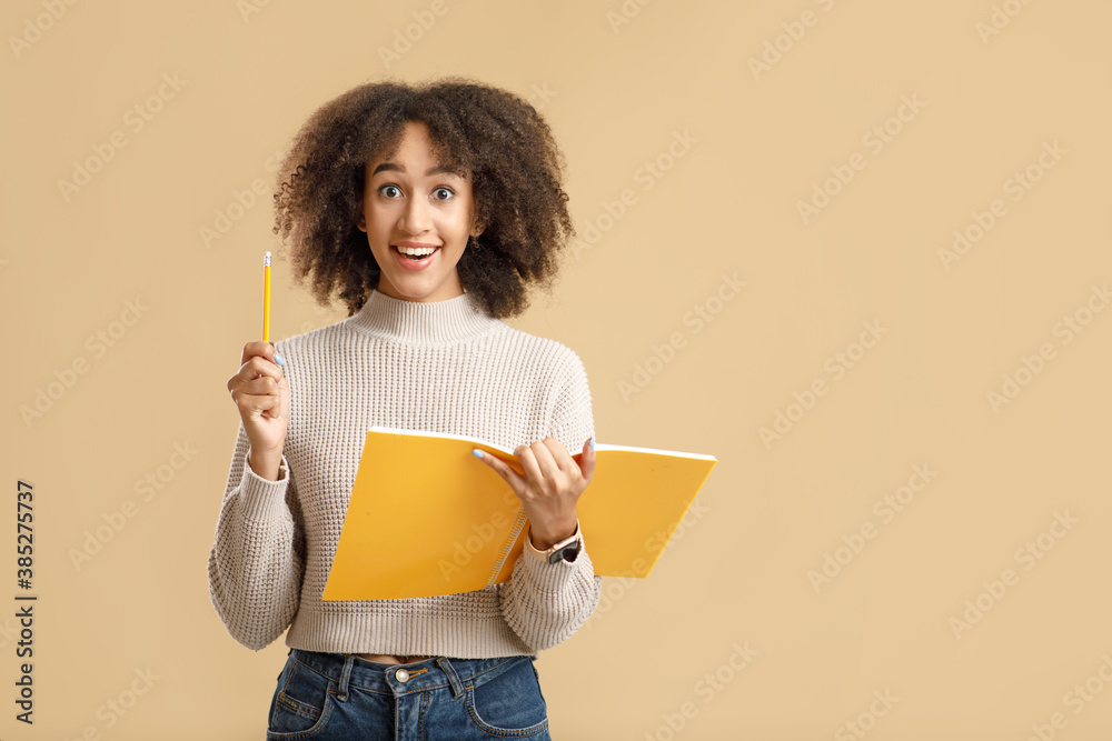 Fototapeta Happy millennial african american woman with open mouth holds notepad and raises pen up