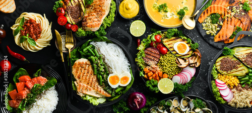 Obraz Food background: pasta, chicken, pumpkin, salad, meat, mushrooms, vegetables. On a black stone background. Top view. Free space for text. - fototapety do salonu